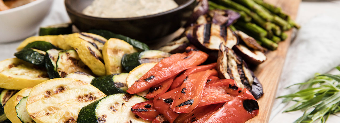 grilled vegetables arranged on cutting board surrounded by herbs with garlic mustard sauce on side